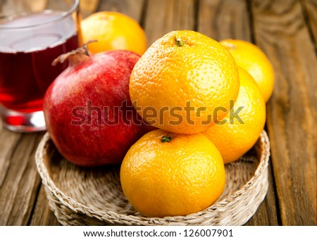 A glass of pomegranate juice on the table with a plate of fruit, tangerine and pomegranate #126007901