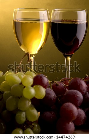 a glass of red and white wine and green and red grape
