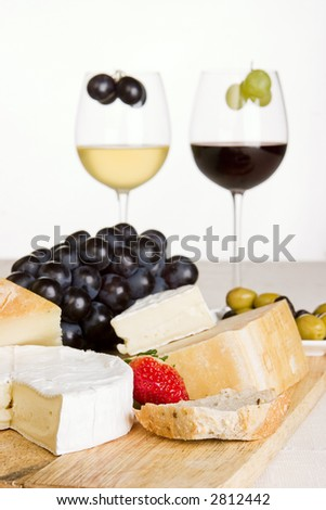 A glass of red and white wine with a cheese board in the foreground