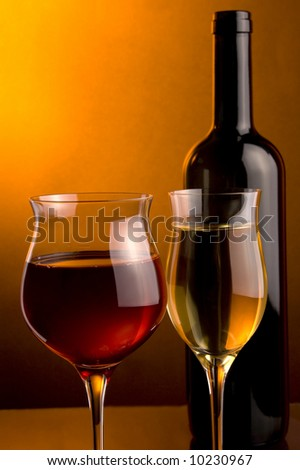 a glass of red of white and a glass of red wine and a bottle