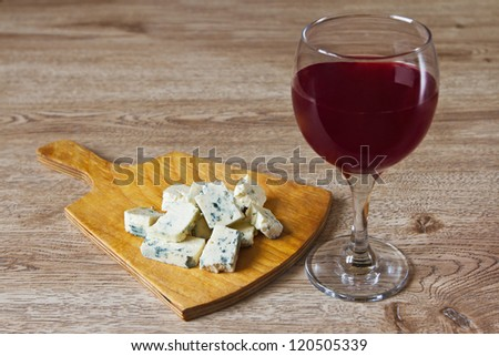 a glass of red wine and cheese on a wooden table