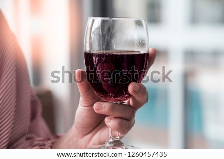 a glass of red wine in woman hand  , rest time.