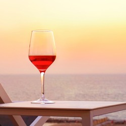A glass of red wine standing on a table near a summer chair against a background of a sea horizon at sunset. A glass of red wine against the background of the evening sea horizon at sunset.