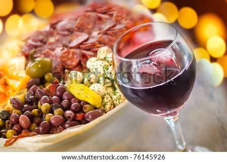A glass of red wine with a platter of Italian antipasto behind and festive lights.