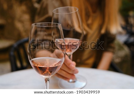 A glass of rose wine in the hands of a girl relaxing on restaurant terrace. Summer holiday. Celebrate and enjoy moment. Alcoholic drink tasting. Romantic evening aperitif. Wine glass closeup