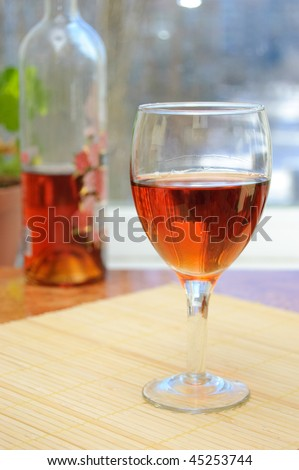 A glass of rosy wine on the kitchen table on a sunny day