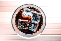 A glass of soda with ice cubes. Chilled drink in a glass.