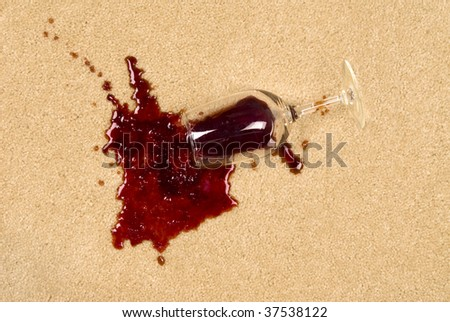 A glass of spilled wine on brand new carpet will leave a stain. - stock photo