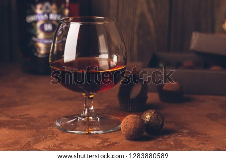 A glass of strong alcoholic drink brandy or brandy and a box of chocolates on a dark background. Copy space. #1283880589