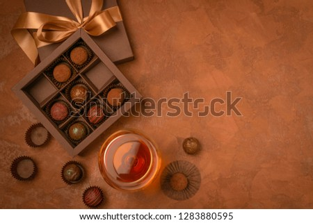 A glass of strong alcoholic drink brandy or brandy and a box of chocolates on a dark background. Flat layout. #1283880595
