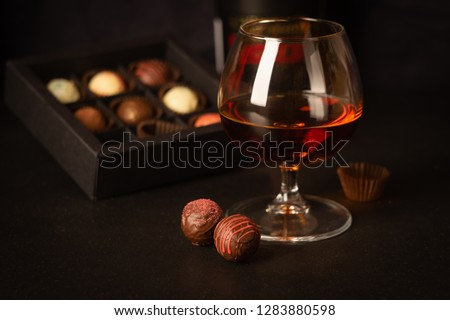 A glass of strong alcoholic drink brandy or brandy and candy made of Belgian chocolate on a dark background. #1283880598