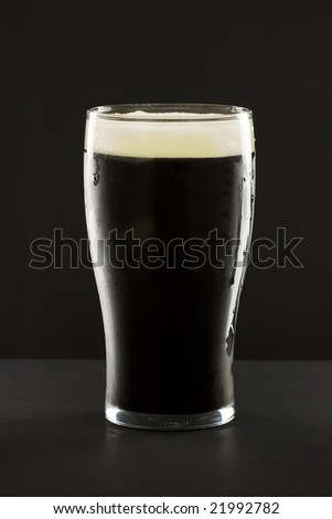 A glass of the famous irish black stout beer against a dark background Stock photo ©