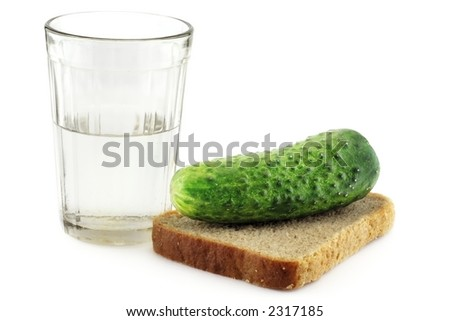 A glass of vodka with a slightly salted cucumber on a rye-bread slice
