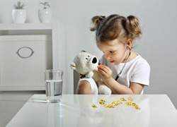 A glass of water and fish oil pills. A child plays doctor in the children's room, a scattering of yellow capsules on the table, a bear cub takes omega 3 pills. a Child with a stethoscope in his ears.