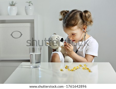 A glass of water and fish oil pills. A child plays doctor in the children's room, a scattering of yellow capsules on the table, a bear cub takes omega 3 pills. a Child with a stethoscope in his ears. Сток-фото ©