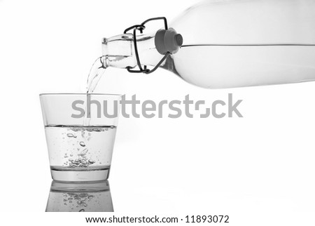 A glass of water being served from a bottle. Isolation with clipping path.