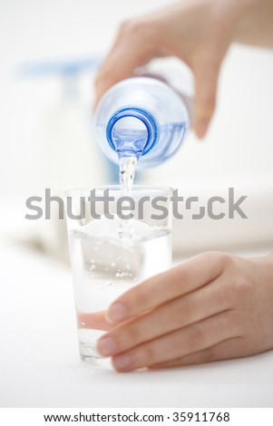 A glass of water pouring from its bottle