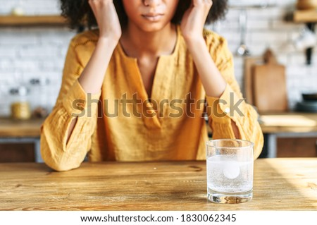 A glass of water with effervescent tablet on the table. Drug, remedy from pain. A woman holds temples with hands on the background, a face is not visible Foto d'archivio ©