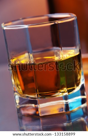 a glass of whiskey against color background