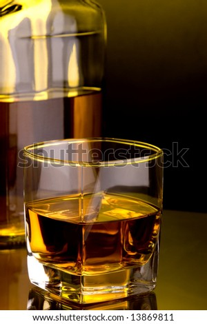 a glass of whiskey and a bottle
