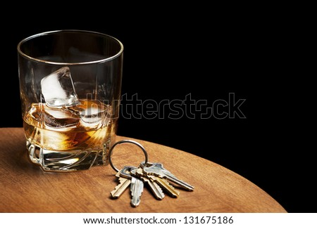 A glass of whiskey and car keys on a table with a black background.