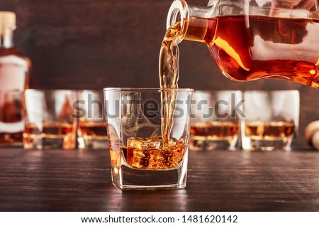 A glass of whiskey on a wooden table in which poured whiskey from a bottle. In the background are four glasses of whiskey, a full bottle of whiskey and a wooden bottle stopper.