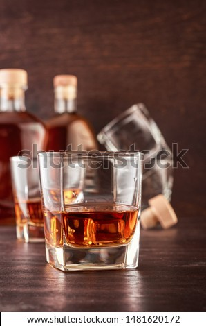 A glass of whiskey with a double portion on a wooden table. In the background, two bottles of whiskey of different shapes, a glass with a portion of whiskey and empty glasses of whiskey.