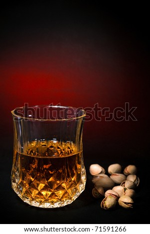 A glass of whisky drink and pistachios, art beverage background, red