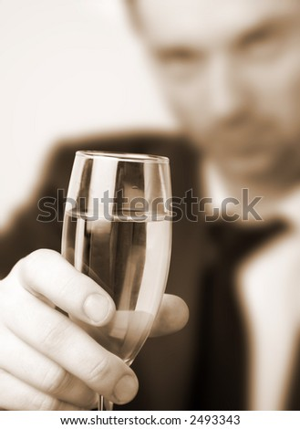A glass of white wine. A classy businessman with a glass of wine. Soft focus. Sepia tone.
