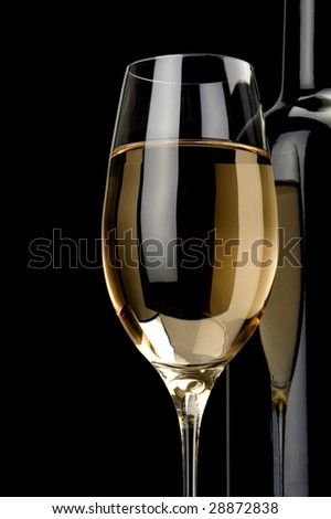 a glass of white wine and black bottle