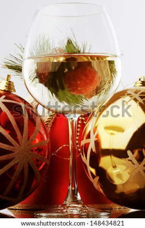 a glass of white wine and Christmas decoration against white background