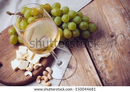 A glass of white wine, grapes, cashew nuts and soft cheese on a wooden board, rustic style background