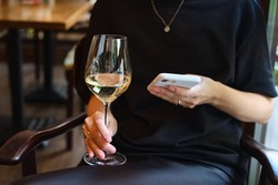 A glass of white wine in the hands of a girl relaxing in a restaurant. Tasting of alcoholic beverages. Summer rest. Romantic evening aperitif. Close-up of a glass of wine. Enjoy the moment