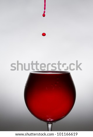 A glass of wine and a drop falling into it. From the drop of fly spray.