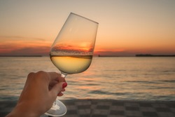 A glass of wine in a woman's hand against the background of the sea. Summer sunset by the sea. A glass of white wine.