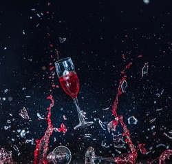 a glass of wine smashed to smithereens. shards of glass, splashes of wine