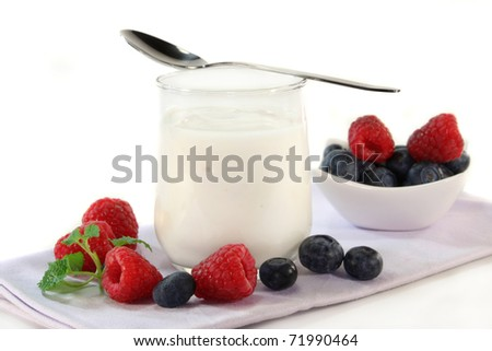 a glass of yogurt and fresh fruit on a white background