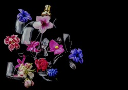 A glass perfume bottle shatters and bright spring flowers and clouds of blue and purple vapor burst out of it against a dark background