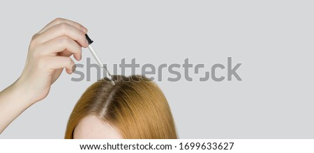 A glass pipette with a hair growth agent is applied to the parting of the hair, red hair. Hair care. Light background, free space for text.