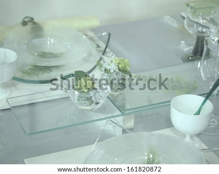 A glass table with an assortment of dishes and two glass birds.