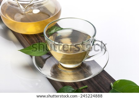 A glass tea pot and glass cup with green leaves on the wood block isolated white at the studio. #245224888