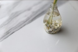 A glass vase with water and stones inside the vase. The vase is placed on a white stone table.