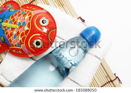 A glass water bottle and fish-shaped metal toy resting on a napkin and a bamboo mat.