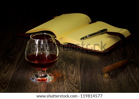 A glass with cognac, cigar and an old book nearby