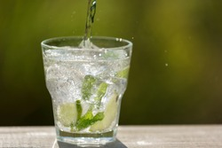 a glass with ice cubes, with lime and with mint, soda water from the bottle, in the open space, sunlight and bokeh, concept
