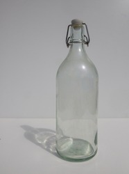 a glassbottle agains a white background With shadows in the sunlight