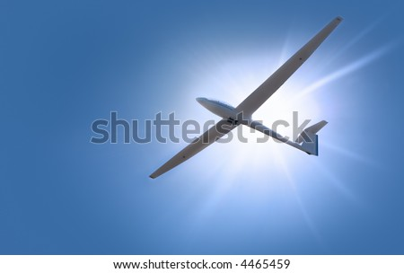 A glider shot from below against a blue sky and sun