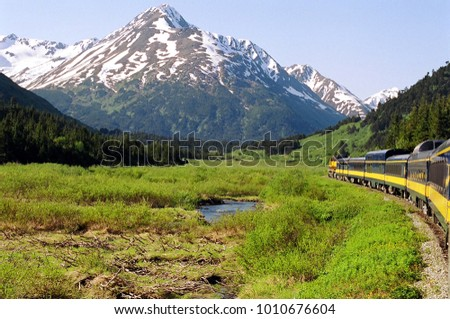 A glorious view of the beautiful Alaskan mountainous wilderness from the rear of a train.