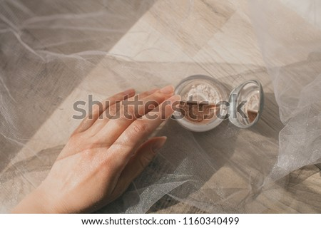 a glossy female young hand glittering in the sun with healthy beautiful nails and a natural manicure takes a box with cosmetics with gold and beige and shiny eye shadow, a gentle pastel picture