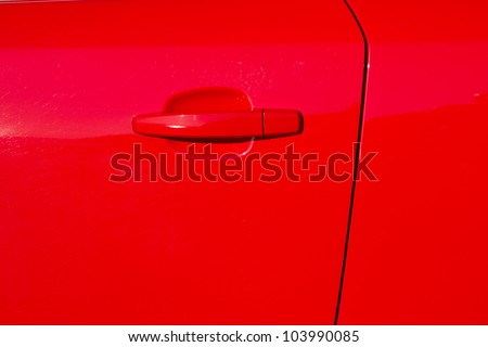 A glossy red painted car door with door edge and a handle.